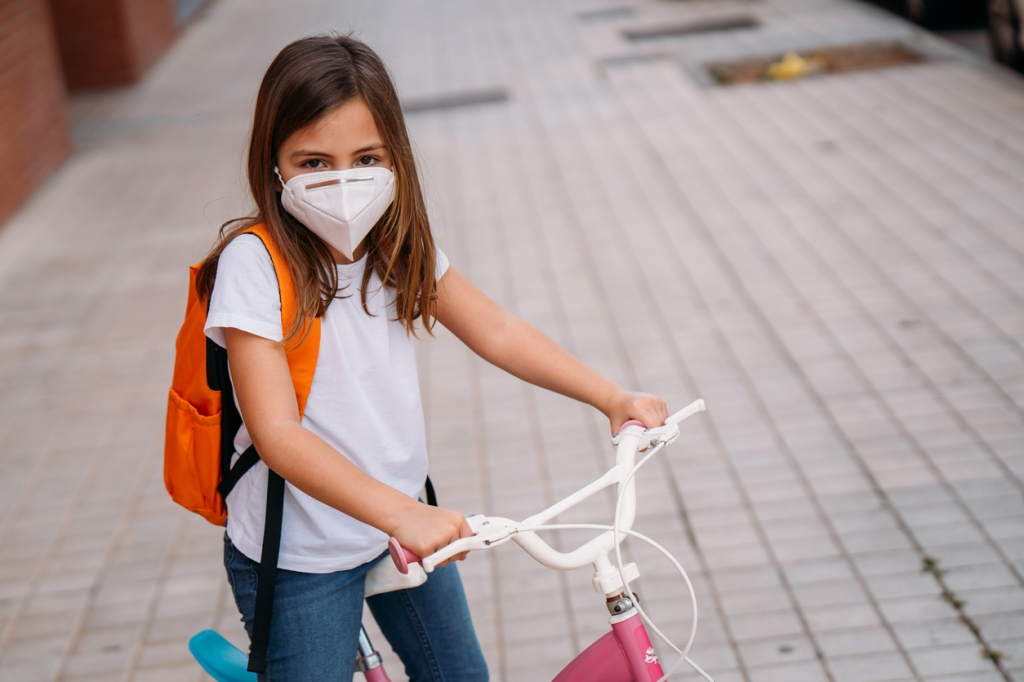 This image has an empty alt attribute; its file name is latina-girl-riding-bike-with-face-mask-overing-during-covid-19-coronavirus.jpg